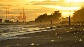 污染产业概念,海滩污染 塑料瓶和其他垃圾在海海滩和工厂用管道输送污染空气反对 免版税库存照片