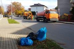 污水清洁通过在一个小欧洲镇的街道上的特别技术手段 橙色汽车和市政工作者清洗ci 免版税图库摄影