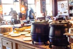 汤加热了有杓子的罐在咖啡馆午餐时间 免版税库存照片