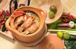 汤姆在泥罐辣汤传统泰国食物烹调的Goong在席子柳条背景的,汤姆Kung,泰国食物泰国 免版税库存照片