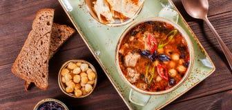 汤用在碗的肉用牛至、鸡豆、胡椒和菜服务用薄脆饼干和面包在黑暗的木背景, 库存图片