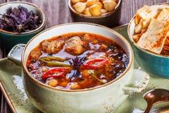 汤用在碗的肉用牛至、鸡豆、胡椒和菜服务用薄脆饼干和面包在黑暗的木背景, 图库摄影
