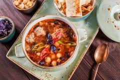 汤用在碗的肉用牛至、鸡豆、胡椒和菜服务用薄脆饼干和面包在黑暗的木背景 库存照片