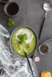 汤用硬花甘蓝和奶油和匙子在灰色背景 免版税库存图片