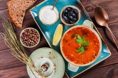 汤用肉、橄榄、草本、柠檬、酸性稀奶油在碗,黑面包和香料在黑暗的木背景,自创食物 图库摄影