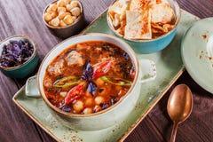 汤用肉、牛至、鸡豆、胡椒和菜服务用薄脆饼干和面包在板材在黑暗的木背景 图库摄影