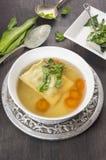 汤用馄饨、红萝卜和ramson在白色板材 库存照片