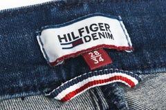 汤米・席尔菲格标签特写镜头在蓝色牛仔裤的 汤米・席尔菲格是生活方式品牌 Hilfiger牛仔布 汤米・席尔菲格蓝色牛仔裤detai 库存照片