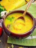 汤纯汁浓汤南瓜用大虾和蘑菇在黑暗的委员会 免版税库存图片