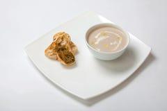 汤纯汁浓汤在一块深白色板材采蘑菇 免版税库存图片