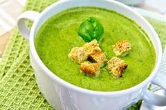 汤纯汁浓汤用油煎方型小面包片和菠菜在餐巾 免版税库存图片