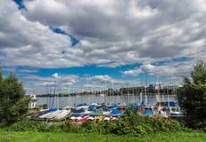 汽艇在海滩水排列了,与中意的风景和多云晴朗的天空在丹戎Benoa,巴厘岛,印度尼西亚 免版税库存照片