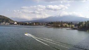 汽艇在背景中横渡河口湖和富士山,山梨县,日本 免版税库存照片