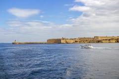汽艇沿Ricasoli堡垒和Ricasoli防堤灯塔通过 库存图片