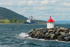 汽艇的人们在海湾跟随挪威军事船在Drobak,挪威 图库摄影