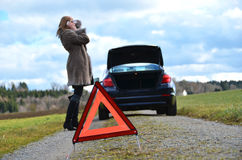 汽车、女孩和警告三角 免版税图库摄影