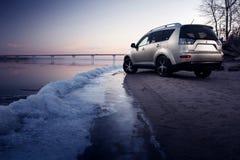 汽车三菱在冰海岸的外国人逗留在冬天日落 免版税库存图片