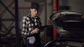 汽车使用数字式片剂的服务技术员审查车里面 汽车修理,维护,人概念 股票视频