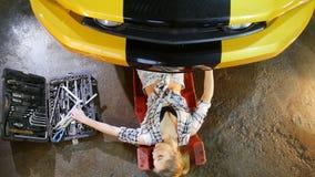 汽车修理公司 从汽车出来的年轻女人,采取板钳并且回来工作 股票录像