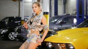 汽车修理公司 年轻女人坐举行板钳和接触的黄色跑车敞篷边缘  股票录像