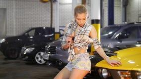 汽车修理公司 年轻女人坐拿着板钳的黄色跑车敞篷  股票视频