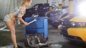 汽车修理公司 年轻女人走到工具箱,弯下来并且采取板钳 股票录像