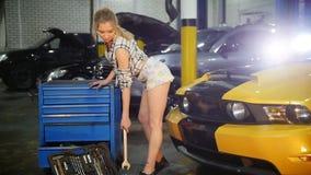 汽车修理公司 年轻女人采取从案件的一把板钳在地板上并且坐汽车敞篷 慢的行动 股票录像