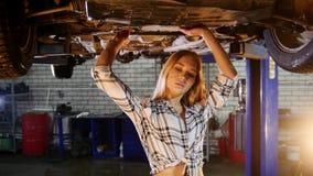 汽车修理公司 汽车推力 年轻女人走在汽车下并且徘徊垂悬在它 股票录像