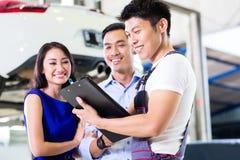 汽车修理师和亚洲顾客夫妇 免版税库存图片