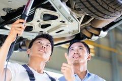 汽车修理师和顾客在亚洲自动车间 免版税库存图片