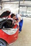 汽车修理师在一辆车的引擎工作在车间- 免版税库存照片