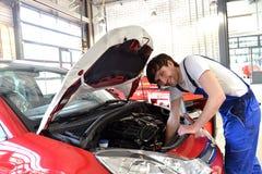 汽车修理师在一辆车的引擎工作在车间- 免版税库存图片