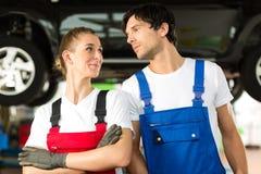 汽车修理师在自动前面的男和女性 图库摄影