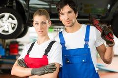 汽车修理师在自动前面的男和女性 免版税库存照片