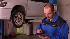 汽车修理师审查电子汽车诊断的结果与片剂的在推力的汽车前面 影视素材