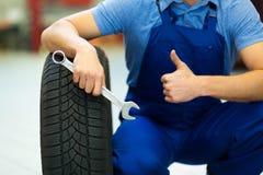 汽车修理师改变的轮胎 免版税库存照片