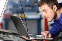 汽车修理师检查电子与膝上型计算机 库存照片