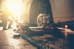 汽车修理师被气动力学的板钳替换被举的汽车车轮在修理公司商店车库驻地,阳光作用 免版税库存照片