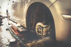 汽车修理师被气动力学的板钳替换被举的汽车车轮在修理公司商店车库驻地 图库摄影