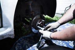 汽车修理 变速轮 司机更换在汽车的轮子 免版税库存图片