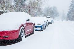 汽车停放和被困住在雪下一条深毯子在意想不到的雪风暴的 免版税库存图片