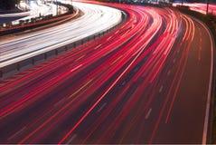 汽车光在一条弯曲的高速公路落后在晚上 免版税库存图片