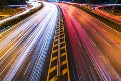 汽车光在一条弯曲的高速公路落后在晚上 图库摄影