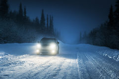 汽车光在冬天森林里 免版税库存图片