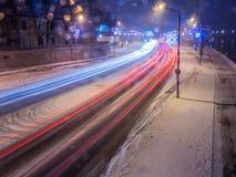 汽车光在冰路的晚上在雪冬天 免版税库存图片