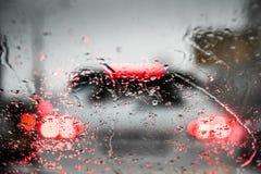 汽车光通过湿挡风玻璃 免版税库存照片