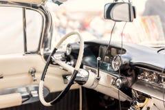 汽车内部减速火箭 方向盘和葡萄酒车驾驶席  经典老automoile仪表板 库存照片