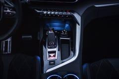 汽车内部:有拨号盘、按钮和齿轮瘤的中央控制台 免版税库存照片