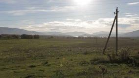 汽车农村风景、山和湖侧面窗视图日落的 驾驶在农村路沿着输电线 股票视频