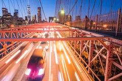 汽车前灯夜光在布鲁克林大桥的 长期风险 免版税库存照片